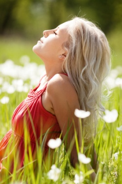 beautiful young blond woman enjoying the Sun on the meadow with white flowers on a warm summer day